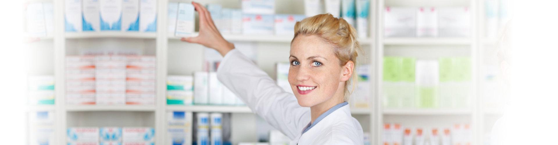 female pharmacist getting medicine from the shelf